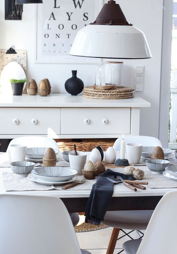 a Scandinavian Easter tablescape with patterned porcelain, dark napkins, simple cutlery and lots of eggs