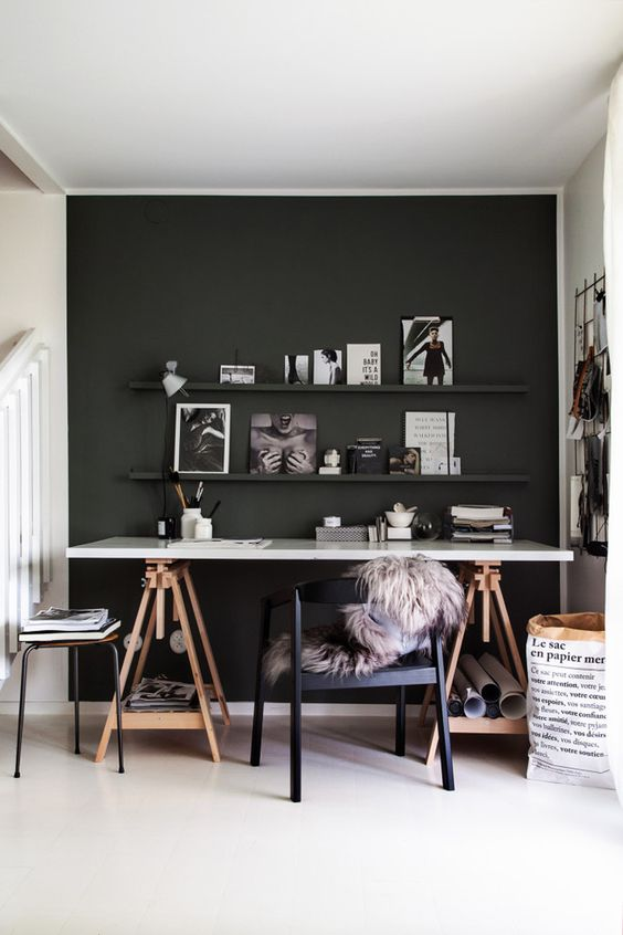 a Scandinavian home office with a black accent wall, a trestle desk with open storage, a navy chair and some artworks and books