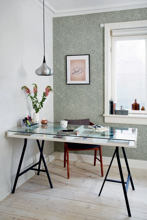 a Scandinavian home office with a glass trestle desk, a leather chair, a pendant lamp and some blooms and floral wallpaper