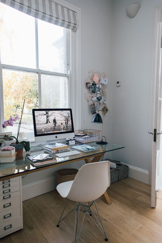 a Scandinavian home office with a wood and glass trestle desk, a white chair and a memo board plus orchids