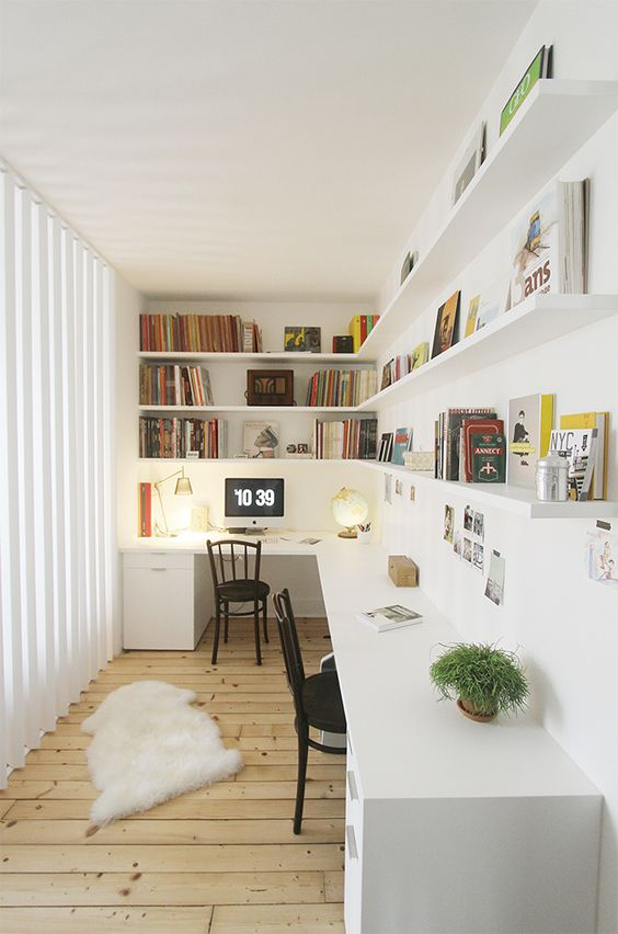 a Scandinavian home office with open shelves, a shared corner desk, black chairs and lots of books and lights