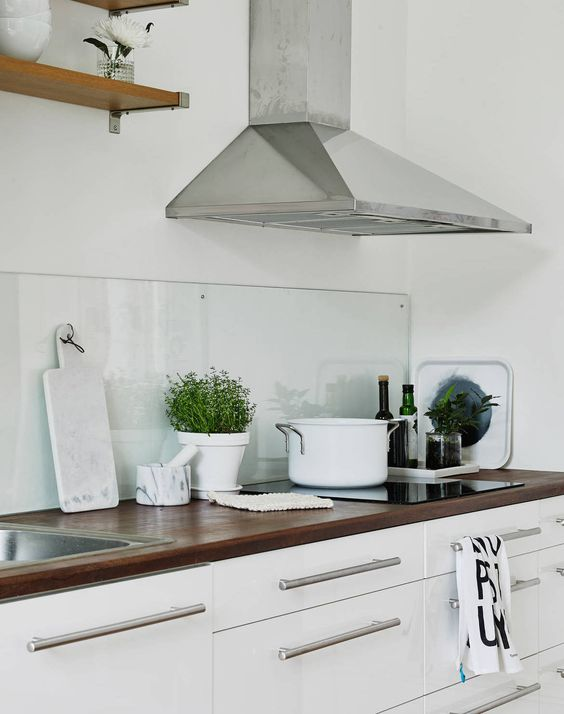 a Scandinavian kitchen with white cabinetry, rich stained countertops, a glass backsplash and stainless steel fixtures