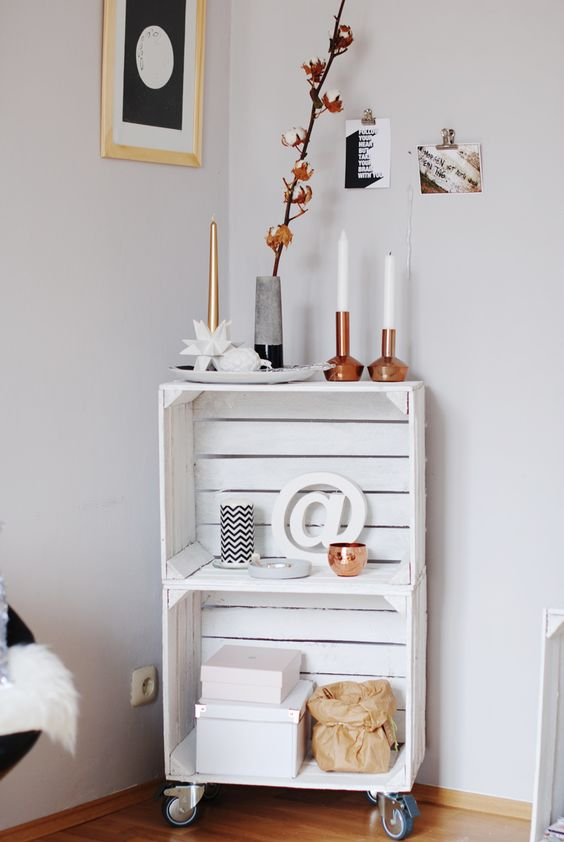 a Scandinavian shelving unit in white made of crates, with candles, vases and other decor is a very smart idea to realize