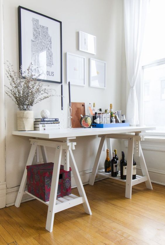 a Scandinavian space with a white trestle desk, where trestle legs are used for storage and the top is used as a home bar