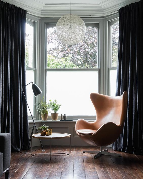 a bay window area as a reading nook, with a leather chair, a round table, some potted plants and havy velvet curtains