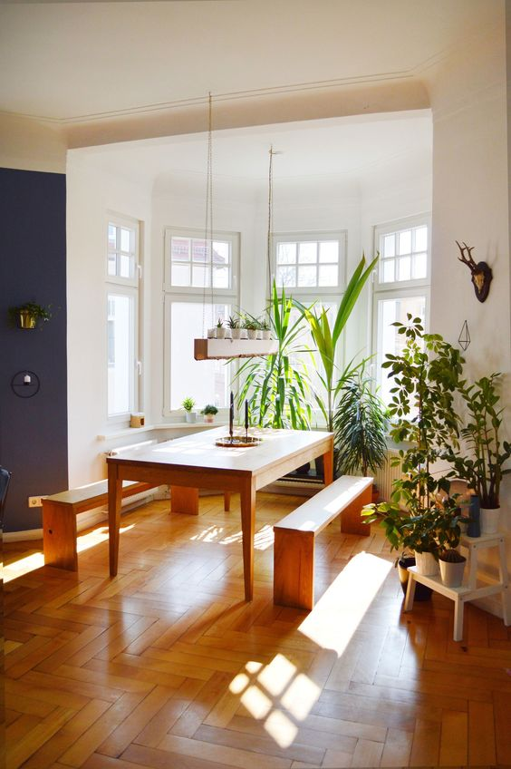 a bay window featuring a dining set with benches and lots of potted plants all over is a very cozy space flooded with light