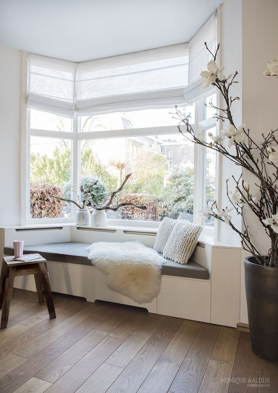 a bay window taken by a contemporary day bed, with pillows and faux fir, with some driftwood in vases is a cool reading nook
