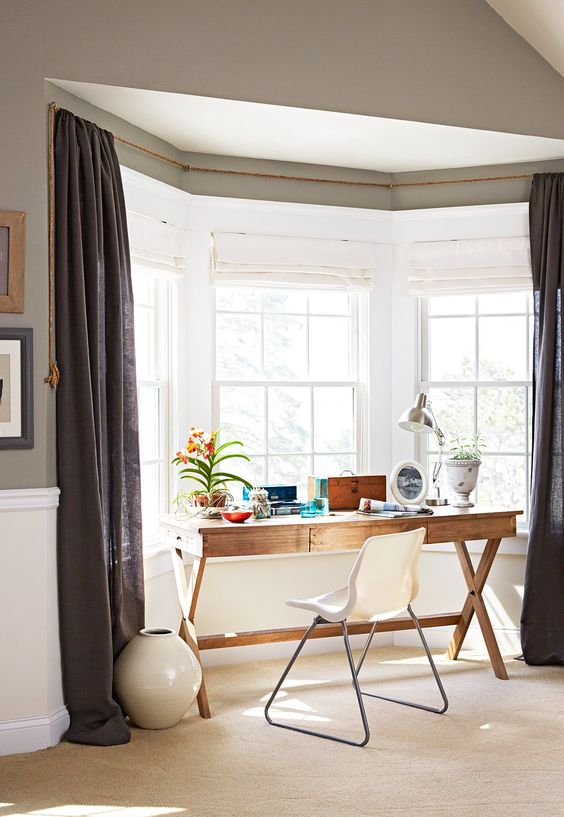 a bay window used as a working space - it fits a wooden trestle desk, a white chair, grey curtains, a box and a lamp is a brilliant idea