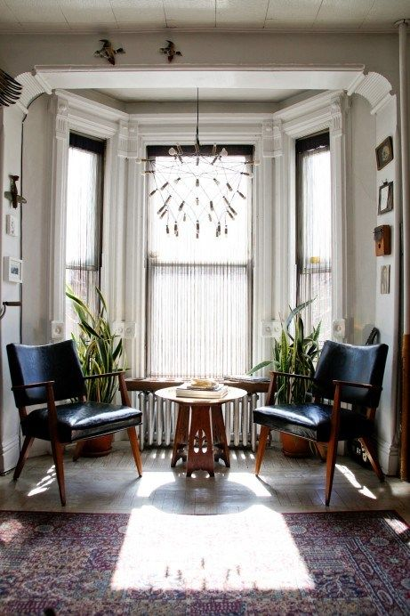 a bay window with a cozy sitting nook, with black chairs, a couple of coffee tables, some plants and a catchy chandelier