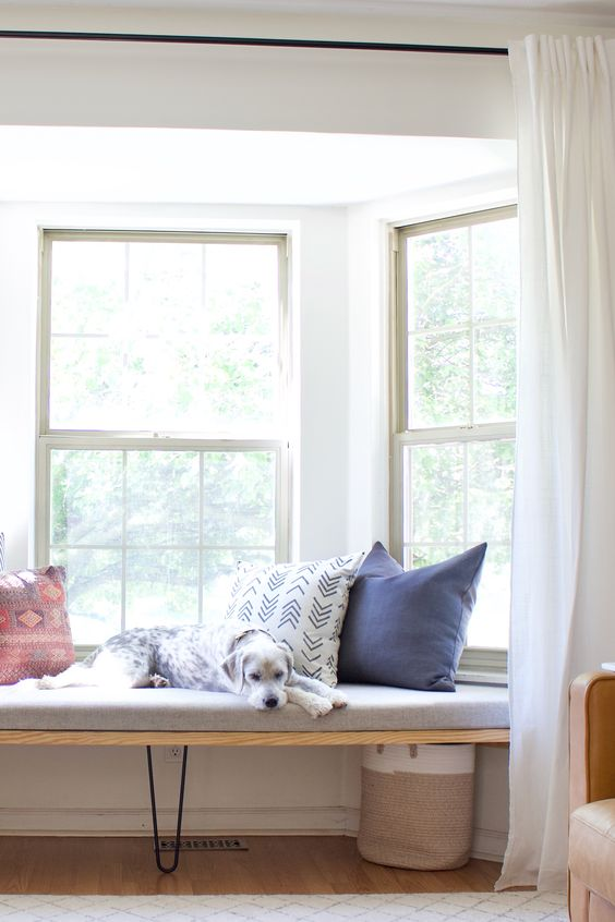a bay window with a fitted daybed, colorful pillows, a basket and curtains to make this space private