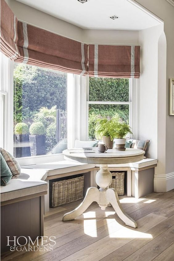 a bay window with a fitted seating area with baskets for storage, a round table, plaid pillows and striped shades