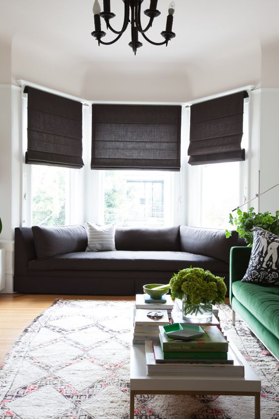 a bay window with a fitted sofa and pillows, dark shades makes this space cozy to be and welcomes a lot