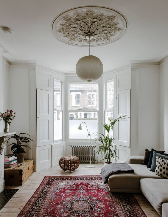 a bay window with a radiator, a potted plant, a lamp and a stool - this is a cool way to use an awkward space