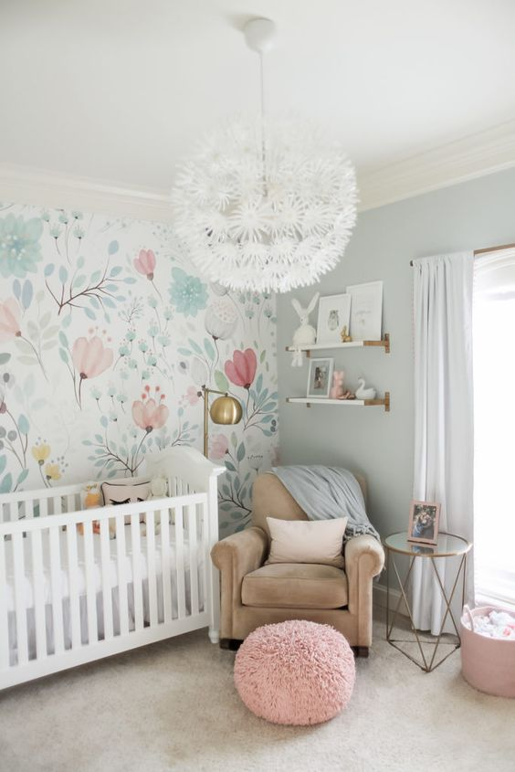 a beautiful and airy nursery with watercolor floral wallpaper, neutral furniture, a floral chandelier and brass touches