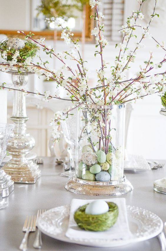 a beautiful and easy spring centerpiece of a large vase with pastel faux eggs and blooming branches is a pretty and chic idea