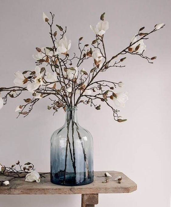 a beautiful spring arrangement of an ombre blue vase and with blooming branches is a stylish centerpiece idea