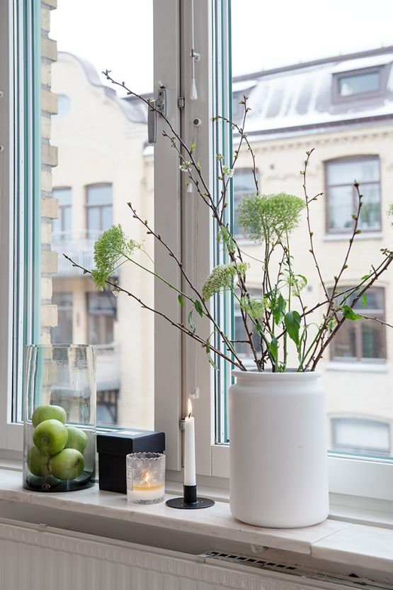 a beautiful spring centerpiece of a white vase with greenery, blooming branches is a lovely decoration for this fresh season
