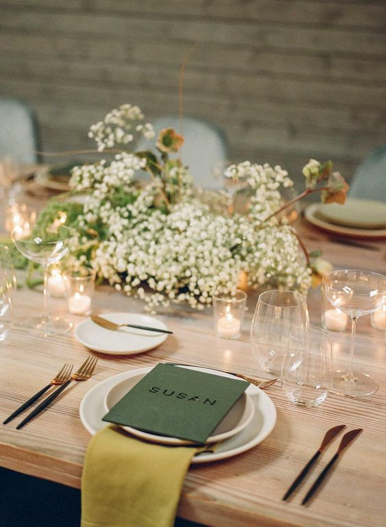 a beautiful spring tablescape with baby's breath, candles, green candles and mustard napkins, elegant glasses