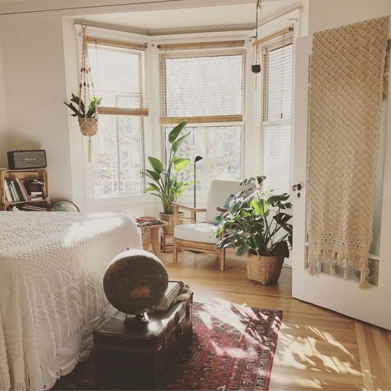 a boho bedroom with a bay window, a chair and some potted plants, the window area is a very cozy nook