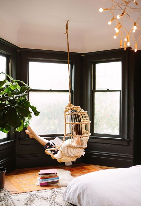 a boho bedroom with a bay window, a hanging chair and some books, this is a great space to relax a bit