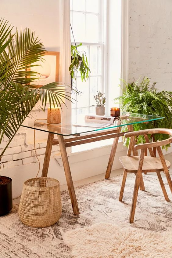 a boho home office with a glass desk, a wooden chair, potted greenery and candles is a very welcoming and cozy space