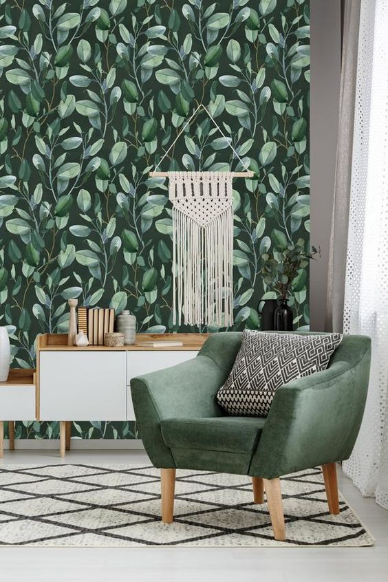 a boho modern space with moody leafy wallpaper, a green chair, a macrame hanging and a white sideboard is bold