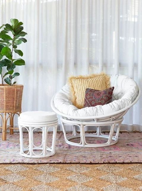 a boho nook with a white rattan chair and a footrest, boho pillows, a potted plant and layered boho rugs