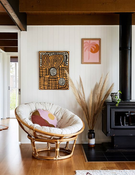 a boho reading nook with a hearth, a rattan chair with pillows, bold artworks, pampas grass and a potted plant