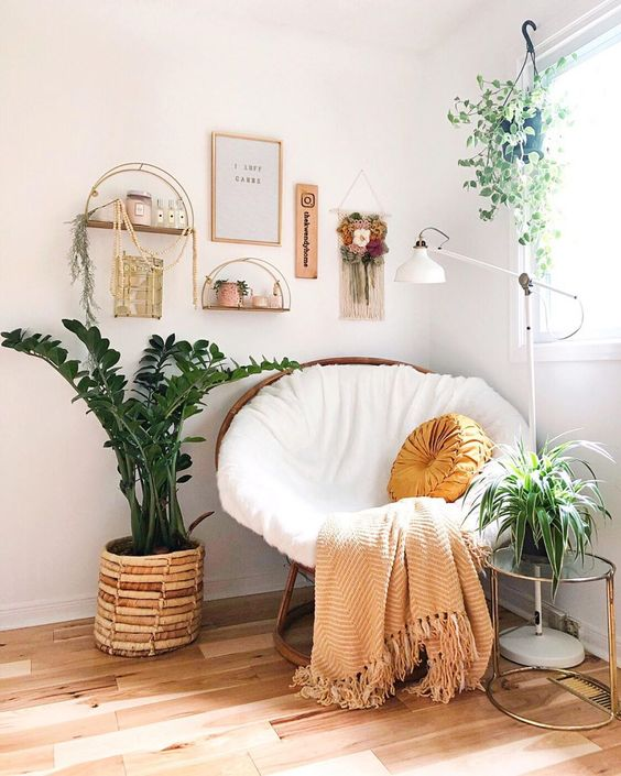 a boho reading nook with a papasan chair, potted greenery, a gallery wlal with shelves and artworks is amazing