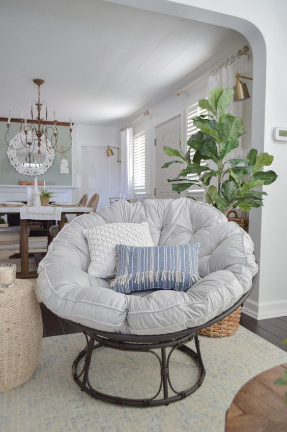 a boho space with a dark rattan papasan chair with pillows and a cushion, a woven ottoan and a potted plant plus a rug