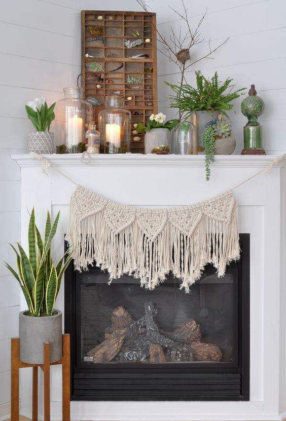 a boho spring mantel with a boho hanging, potted succulents, blooms and greenery, candles in jars and a modd and pebble collection