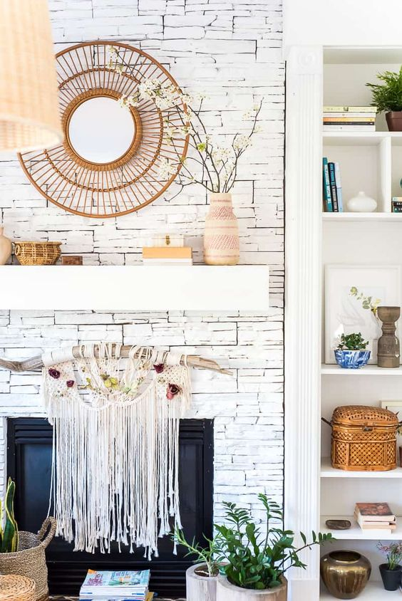 a boho spring mantel with a sunburst mirror, blooming branches in a boho vase, baskets and a boho hanging over the fireplace