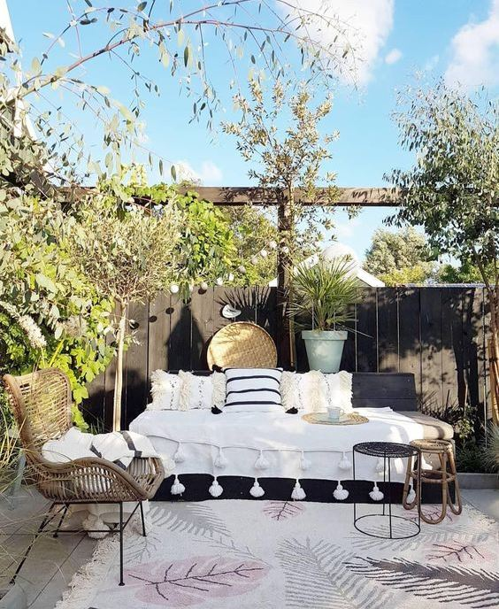 a boho spring terrace with a daybed with pillows, rattan furniture, potted and growing trees and pretty accessories