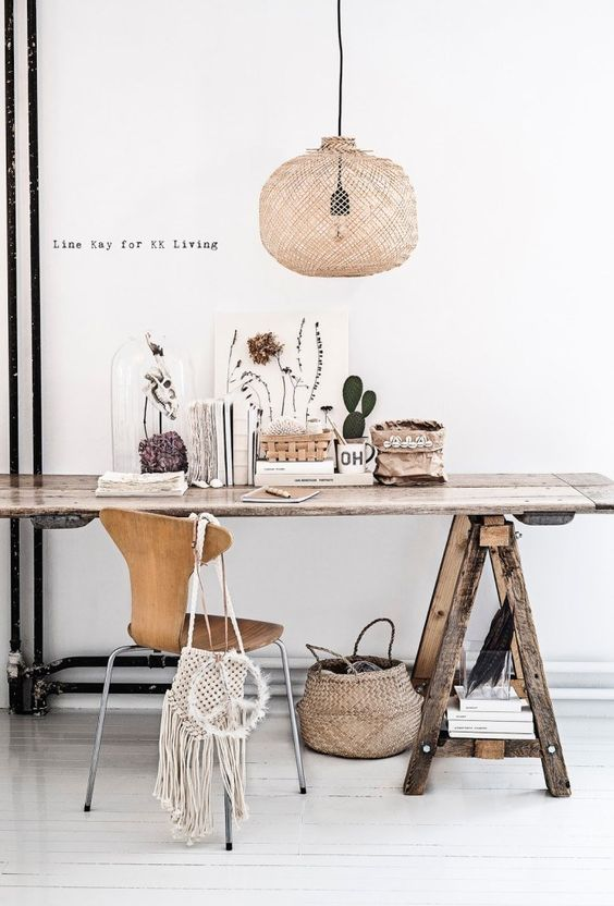 a boho work space with a rough wooden trestle desk, a wooden chair, a woven pendant lamp, blooms and cacti