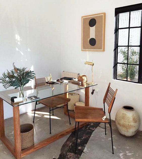a boho working space with a glass and wood desk, a leather chair and potted greenery, some vases and baskets