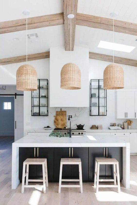 a bold and chic kitchen with white cabinets, a black kitchen island with a marble countertop, a marble backsplash and wicker lamps