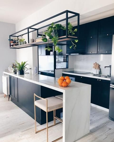 a bold contemporary kitchen in black and white, with a marble backsplash and countertops, an open shelf and some greenery