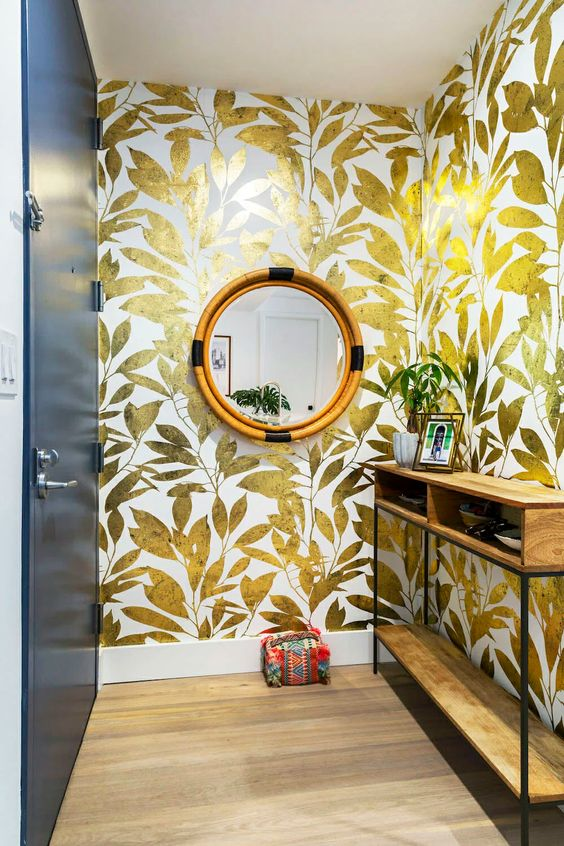 a bold entryway with gold botanical wallpaper, a storage console table, a round mirror and a little colorful doorstop