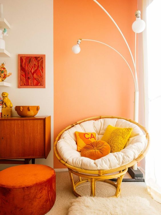 a bold mid-century modern reading nook with a papasan chair with bright pillows, a creative floor lamp, a rust ottoman and a bold artwork