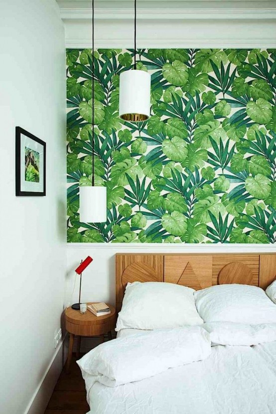 a bold modern bedroom with tropical leaf wallpaper, a catchy wooden bed and round nightstands plus pendant lamps