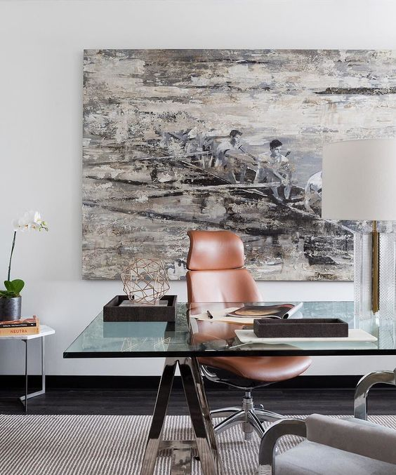 a bold modern home office with a glass and metal trestle desk, leather chairs, a table lamp and a statement artwork