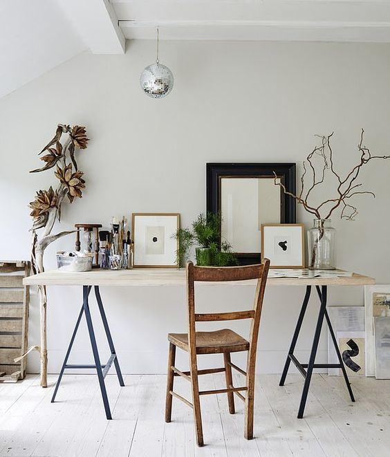 a bold modern working space with a modern trestle desk, a wooden chair, some artworks and branches and a branch with dried blooms