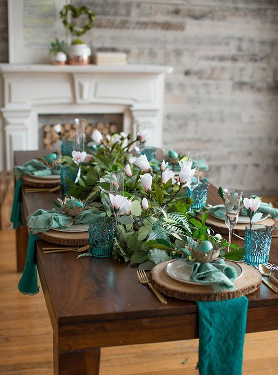 a botanical Easter tablescape with teal and green napkins, greenery, pink blooms, nests with green eggs