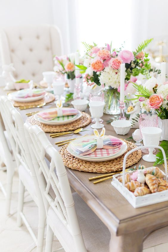 a bright Easter table with woven placemats, colorful napkins and plates, bold pink blooms and glasses plus bunny ears and eggs