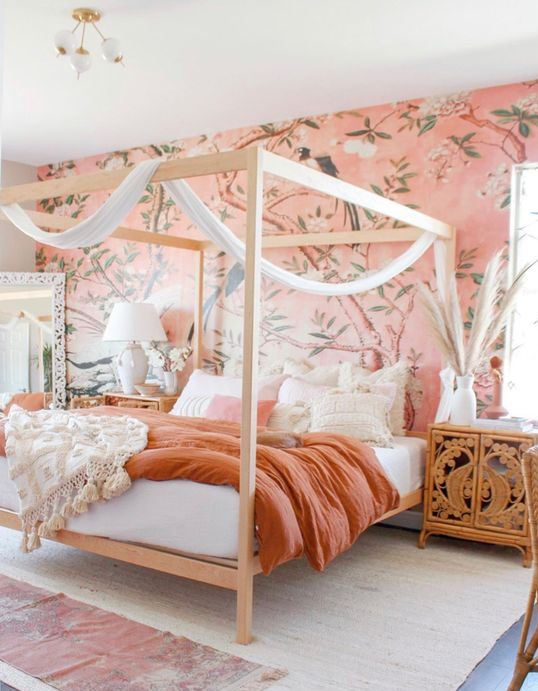 a bright boho bedroom with pink floral wallpaper, a canopy bed, carved furniture, a mirror and pampas grass