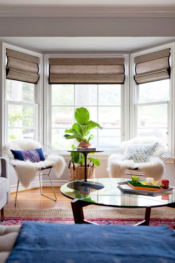 a bright boho sitting zone by the bay window - metal chais with pillows and faux fur, a potted plant and a window with Roman shades