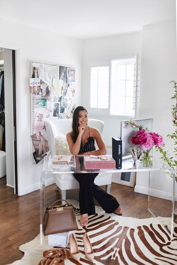 a bright girlish working space with a sheer glass desk, a white chair, a memo board and a faux zebra rug for a touch of whimsy