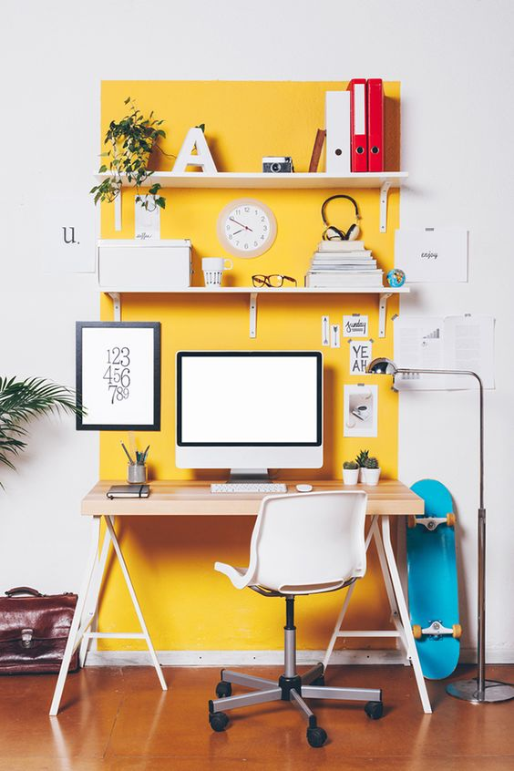 a bright home office with a yellow accent wall and shelves, potted greenery and books, a trestle desk and a white chair plus colorful touches