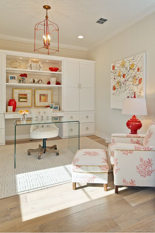 a bright home office with built-in storage units, a glass desk and a bright printed chair and ottoman plus a bold artwork