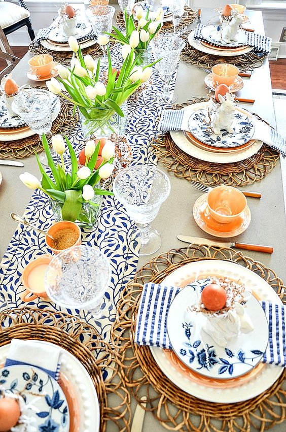 a bright rustic Easter tablescape with printed linens, rattan chargers, white tulips, candles and eggs plus floral plates